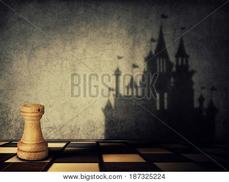 Rook chess piece casting a shadow in shape of a castle on a concrete wall. Business aspirations. Magical transformation.