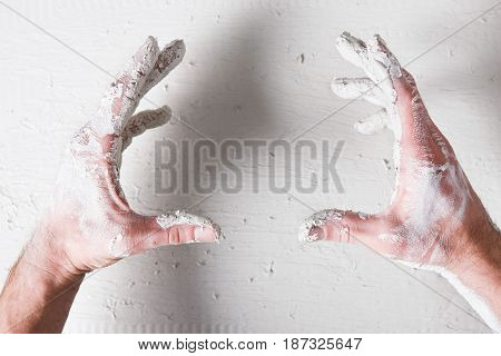 Repair background. Worker dirty hands hold something on white plaster surface, flat lay, void. Building backdrop with free space for advertisement or commercial