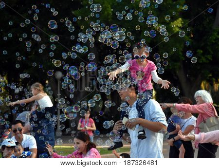 Sydney Australia - Apr 23 2017. Kids catching and having fun and with soap bubbles in Hyde Park (Sydney NSW Australia).