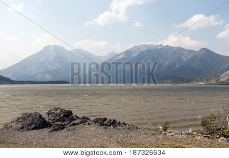 Mountains visible through the haze of forest fire smoke along the banks of the Bow River in Alberta Canada.