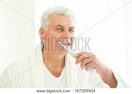 Senior man cleaning teeth at home