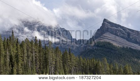 Two mountain peaks in Kananaskis country. One veiled by clouds the other not.