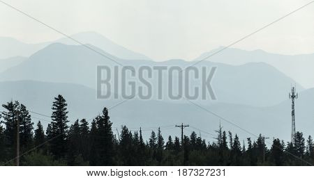 The Canadian Rockies barely visible through the haze of forest fire smoke.