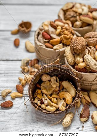 different nuts in a plate closeup on white wooden background , concept of healthy protein power