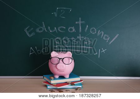 Piggy bank with books and coins on chalkboard background. Education costs concept