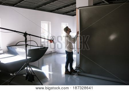 Assistant setting equipment in photostudio before photo session. Professional photographer is adjusting studio for photographing.
