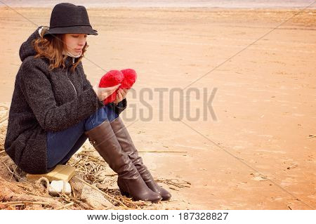 A young woman in a hat and coat sits on the shore of the bay on a fishing net with a plush heart in her hands.