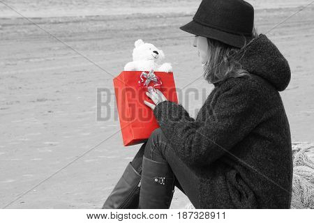 A young girl wearing a hat and coat sits on a fishing net on the beach and looks at the gift in her hand, a bright red gift bag and a teddy bear