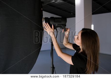 Assistant of photographer adjust light in studio. Beautiful woman with camera is setting photographing equipment getting ready for a photo shoot