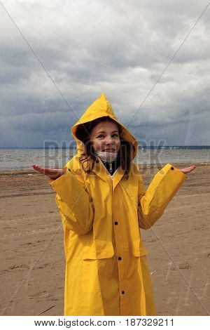 A young girl in a yellow raincoat is standing in the rain on the shore of the bay, dark clouds with rain, hands raised, early spring, bad weather, good .