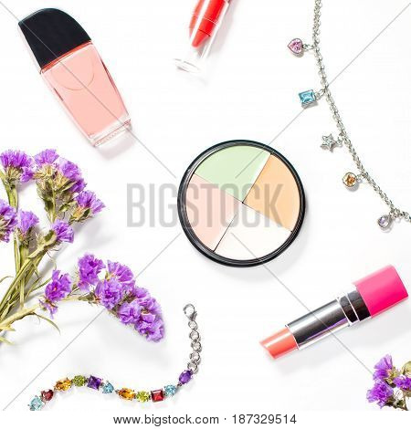 Make up products and jewelry on a white background, overhead view