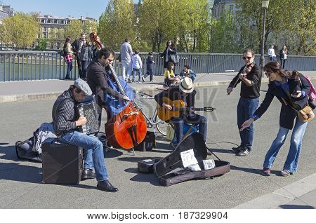 PARIS FRANCE - APRIL 2 2017: Street musicians in retro style on a Saint-Louis bridge Paris France. A sunny day in early April.
