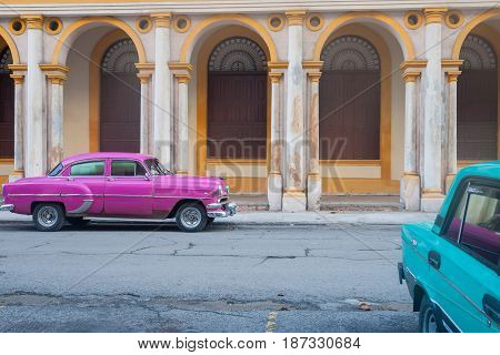 Havana, Cuba - June 29, 2012; Urban street in Havana with parked old vintage cars brightly painted in pink and blue in front of arches of colonial style portico