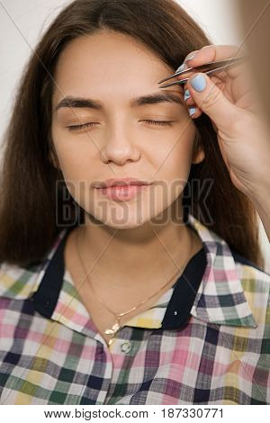 Vertical indoors shot of unrecognizable visage deleting eyebrows with pincers. Perfect eyebrow shape tutorial, makeup artist portfolio concept.