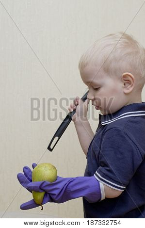 A little boy wearing glove beating a pear with ladle vertical shot concept of misbehaving