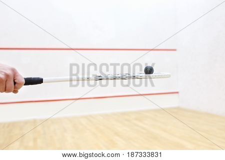 hand holding squash racket and ball. Racquetball equipment. Photo with selective focus. Player prepares to serve a squash ball. Closeup of male hand serving ball