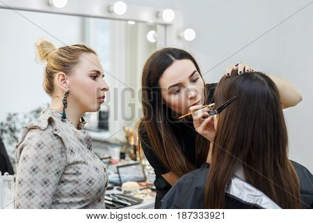 makeup teacher with her student girl. Makeup tutorial course at beauty school. Visagiste applying makeup on the eyes. Makeup master class
