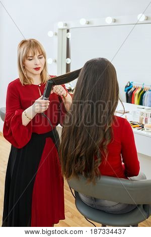 professional stylist using curling iron and doing curls women's hair. Hair curls in beauty salon. Backstage photo stylist working in studio dressing room