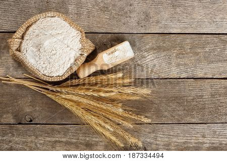 wholegrain flour in burlap bag and wheat ears on wooden table. Top view. Copy space. Baking background. Flour