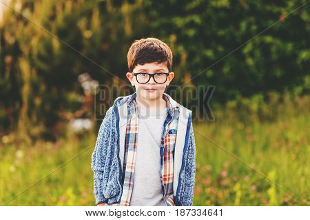Outdoor portrait of cute 6 year old little boy in the park