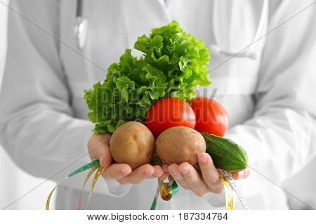 Young female nutritionist holding fresh vegetables and measuring tape, close up