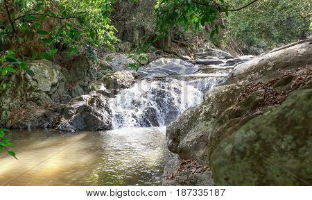 Landscape view of cascade and water stream with the sunbeam in summer Thailand trekking and hiking concept.