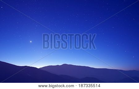 Majestic mountains landscape with shining stars over clear sky