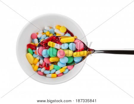 Diet concept. Spoon and bowl full of assorted pills on white background
