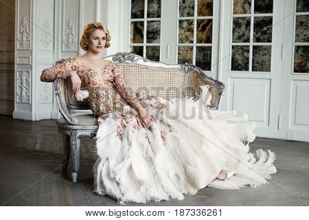 Young beautiful lady in luxury golden dress