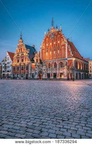 Riga, Latvia. Schwabe House And House Of The Blackheads At Town Hall Square, Ancient Historical Landmark And Popular Touristic Showplace In Summer Evening. Night Illuminations