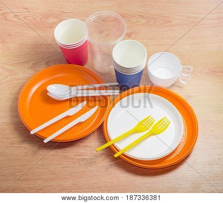Orange and white disposable plastic plates different sizes plastic disposable forks spoons and knives disposable plastic and paper cups on a wooden surface