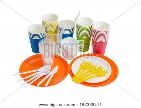 Orange and white disposable plastic plate spoons forks and knives disposable paper cups in different colors different white and transparent disposable plastic cups on a light background