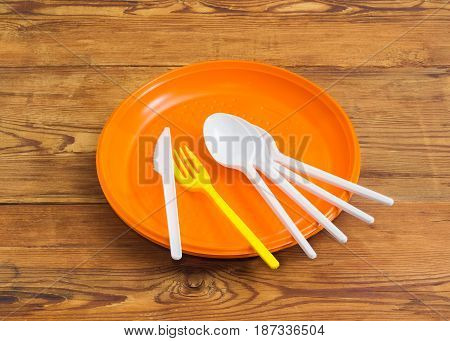 Several disposable plastic white spoons knife yellow fork on the pile of the orange plastic disposable plates on a surface of the old wooden planks