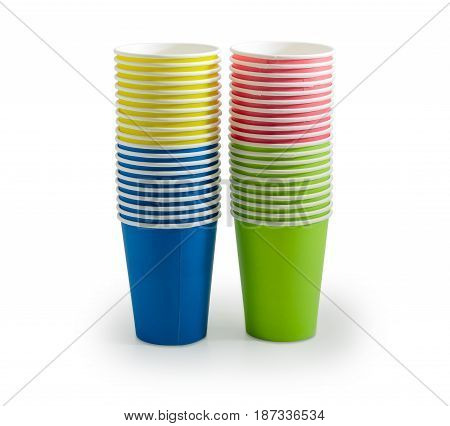 Two piles of the disposable paper cups in red green blue and yellow colors on a light background