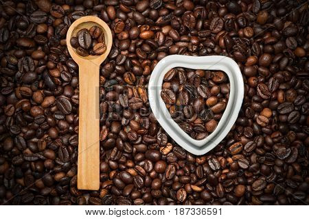 I Love Coffee - Roasted coffee beans in a heart shaped bowl and in a wooden spoon on a background with many coffee beans
