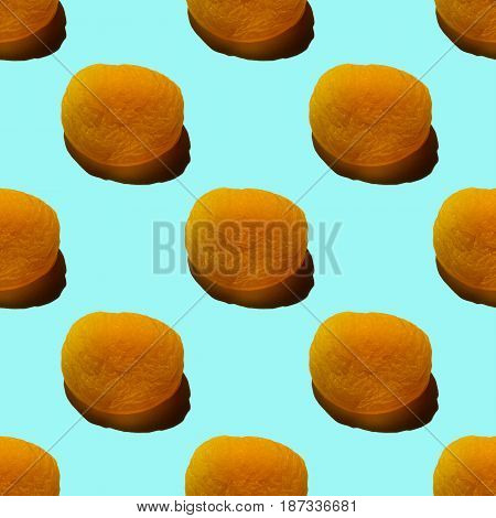 Seamless pattern of dried apricots isolated on light turquoise background.