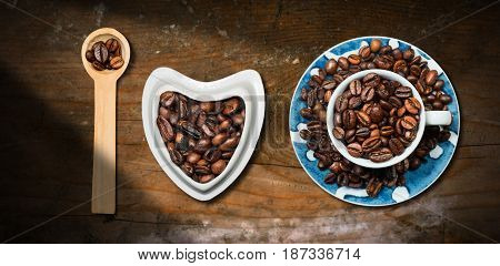 I Love Coffee - Roasted coffee beans in a heart shaped bowl in a wooden spoon and in a coffee cup. Wooden table