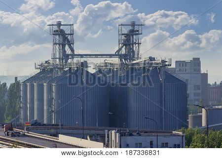 Grain storage system with corrugated steel storage bins and grain distribution system in the grain terminal of the seaport on the background of sky with clouds