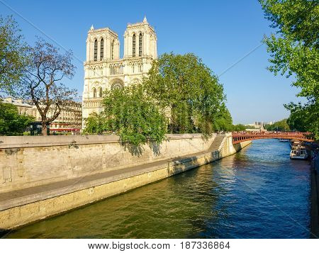 West facade of the Cathedral Notre-Dame de Paris with river Seine and her embankment in the foreground in the spring evening