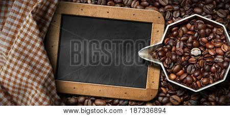 Old italian coffee maker (moka pot - top view) with roasted coffee beans and an empty blackboard with copy space