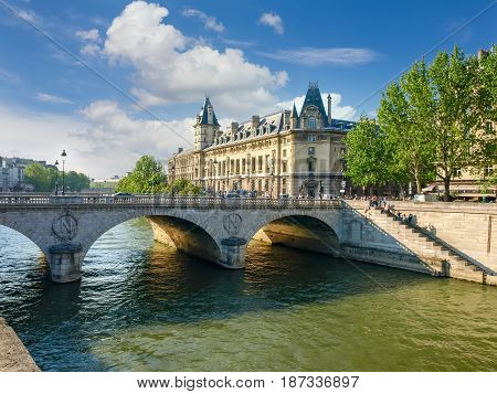 Southern facade of the Palace of Justice with towers river Seine her embankment and bridge in the foreground in Paris