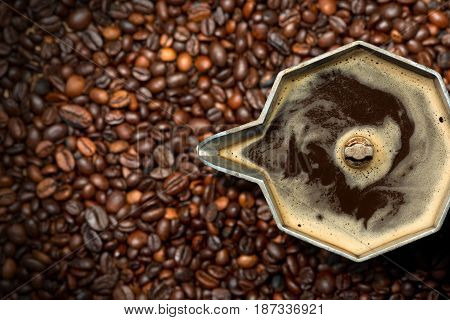 Closeup of an old italian coffee maker (moka pot - top view) with roasted coffee beans on background