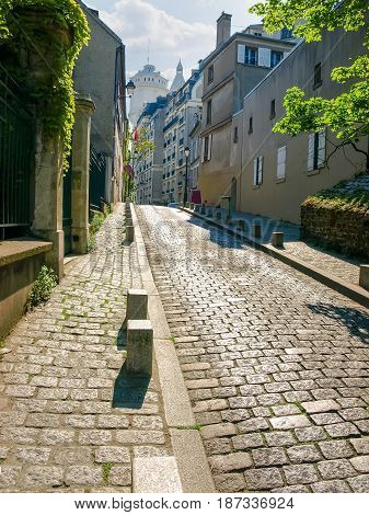 Old street covered with paving stones on the Montmartre hill in Paris France