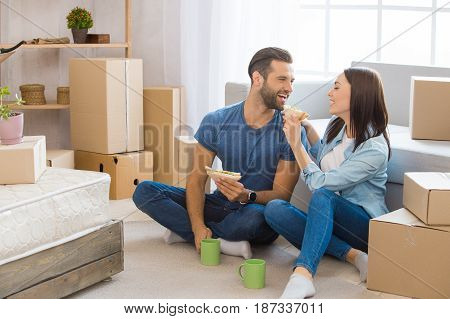 Young couple man and woman moving to a new apartment together relocation eating sandwich