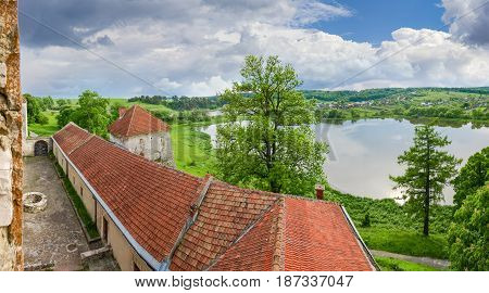 View from the window of the Svirzh Castle built in the 15th century on to the other castle buildings lake and the surrounding countryside in springtime in Lviv region Ukraine