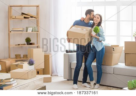 Young couple man and woman moving to a new apartment together relocation