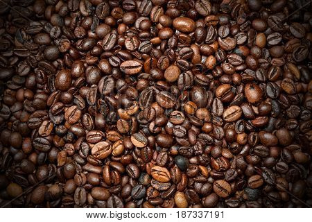 Background with roasted coffee beans with dark shadows