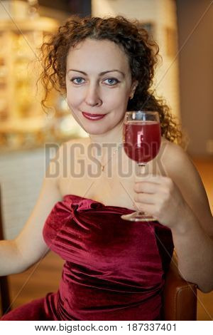 Smiling woman in red slinky evening dress with glass of beverage sits at bar counter.