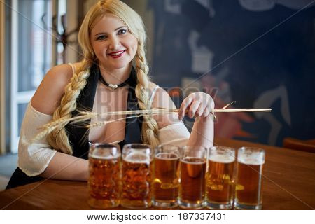 Smiling blonde woman stands holding spikelets in hand and leaning elbow on bar counter with beer mugs in cafe.