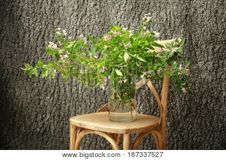 Glass vase with branches of blooming tree flowers on wooden chair